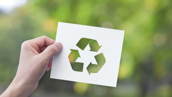 Environment Concept Hand Holding White Paper With Recycle Symbol on Green Bokeh Background